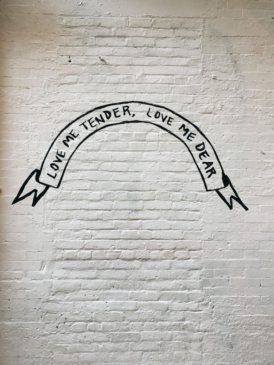 """A white painted brick wall with a black banner painted on it. It reads """"love me tender, love me dear"""""""