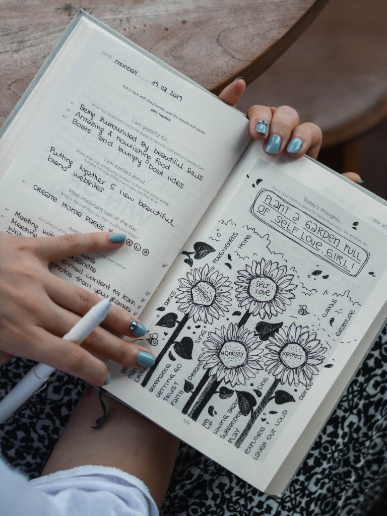 "Girl writing in her journal. It reads ""plant a garden full of self love, girl!"" and has drawings on sunflowers."