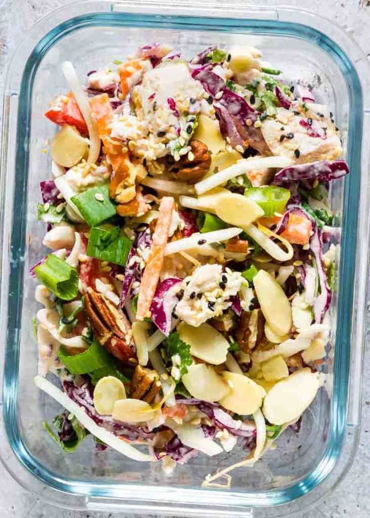 A glass container holds crunchy turkey salad and veggies with dressing