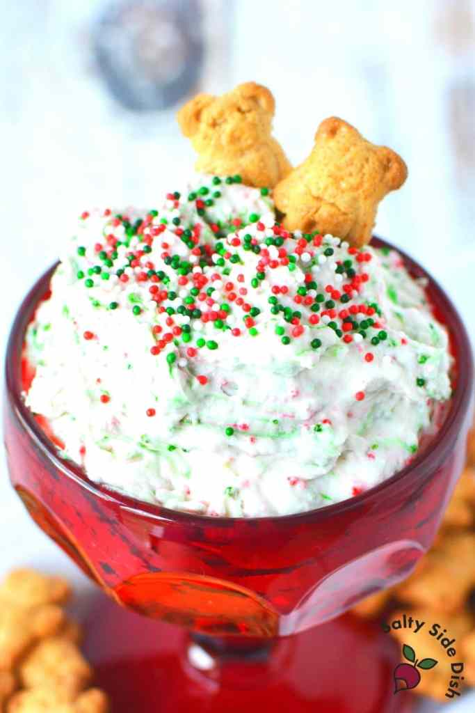 A red dessert glass holds fluffy, white cookie dough dip with red and green sprinkles mixed throughout. It is topped with red and green sprinkles and two Teddy Graham cookies.