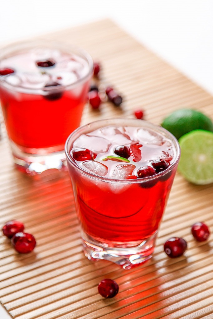 A bright red cranberry margarita drink sits on a bamboo mat. It is garnished with whole cranberries, lime slice and ice cubes. Limes cut in half sit to the side.