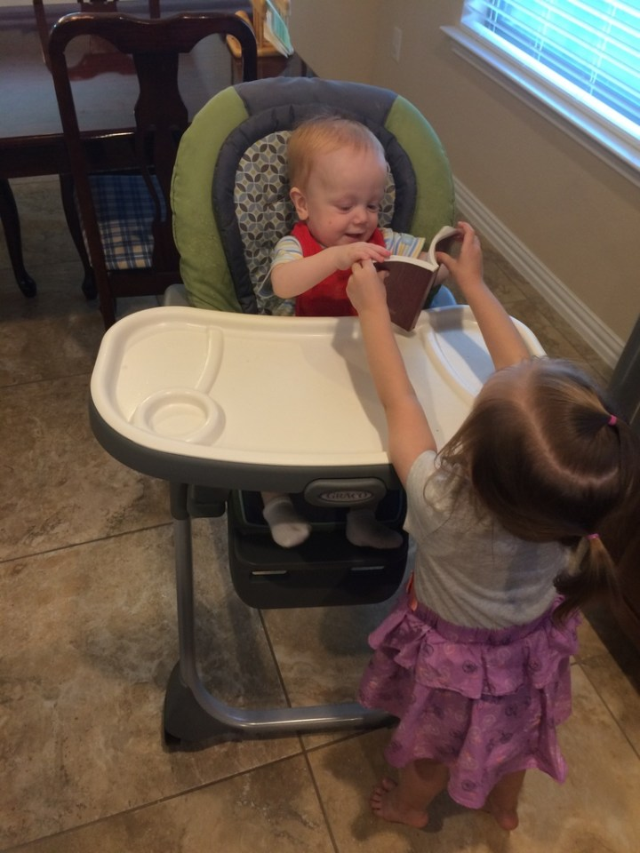 Eliza helped James read the scriptures while mommy was preparing dinner.