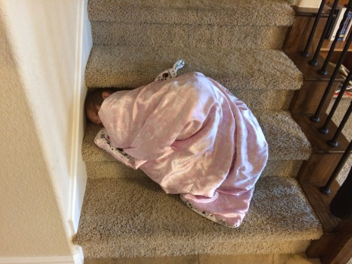 Eliza pretending to sleep on the stairs