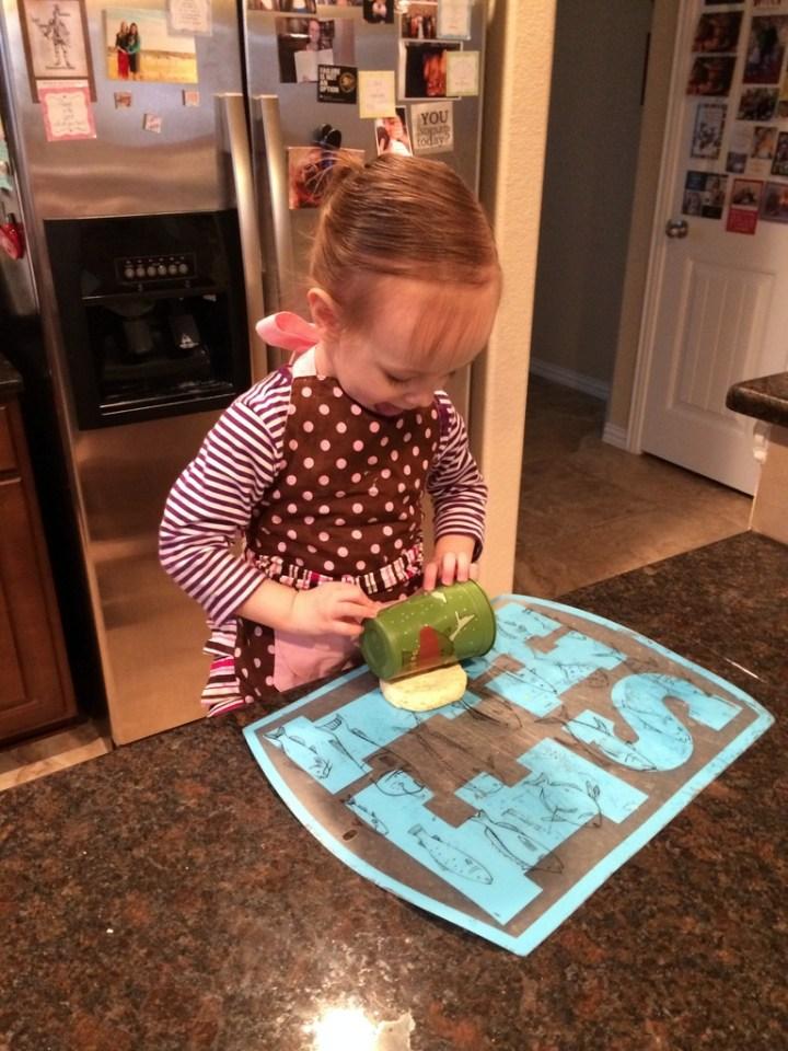 Eliza helping Sarah makes piggies in a blanket