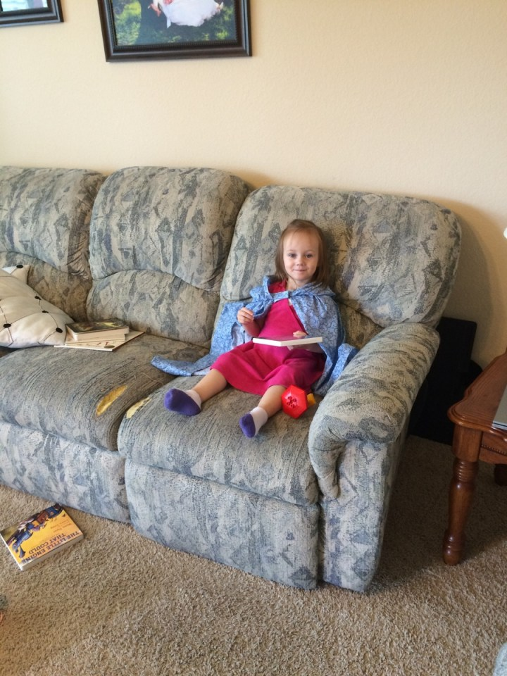 Eliza loves the cloak that Sarah made her for her birthday. She also loves to read.
