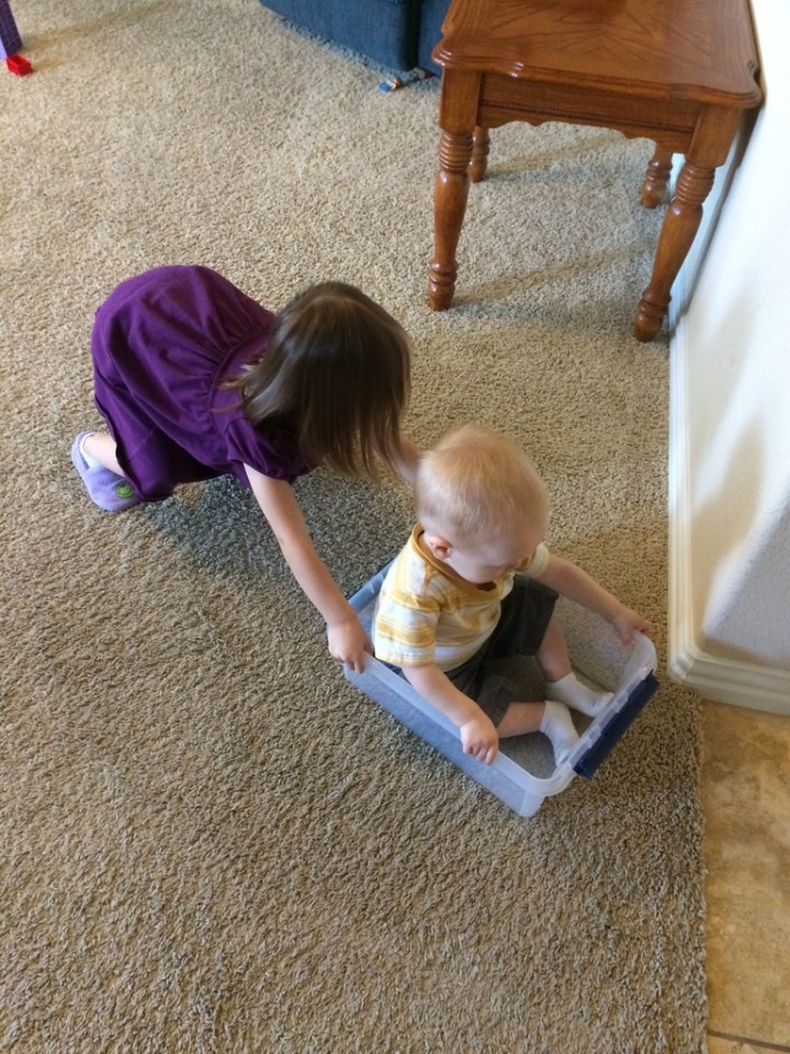 Eliza has started playing train lately and asking mommy to push her across the floor in different boxes. This week she pushed James.
