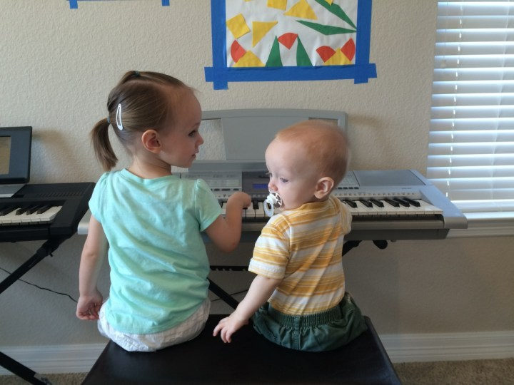 Eliza and James playing the keyboard at music class.
