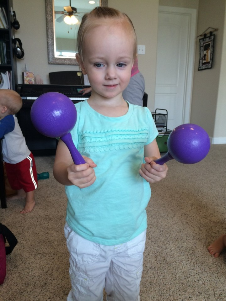 Eliza with her maracas at  music class.