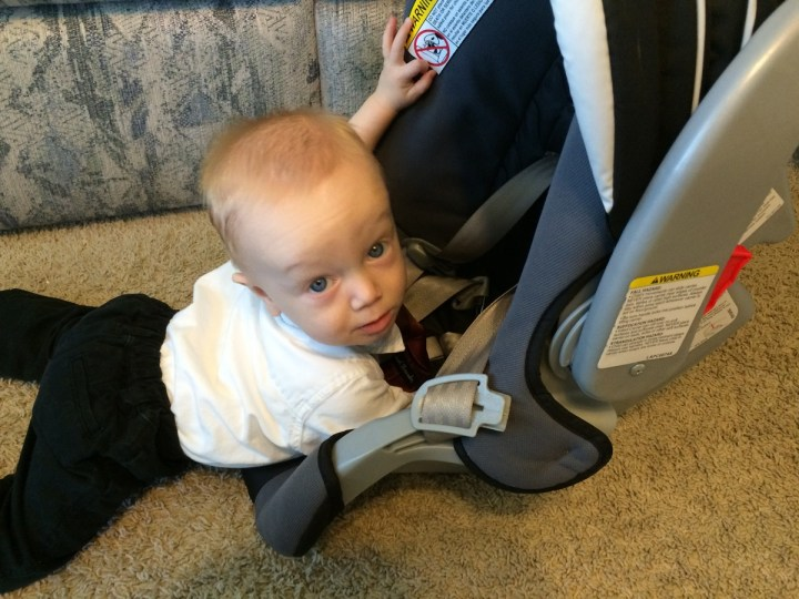 James playing in his carseat.