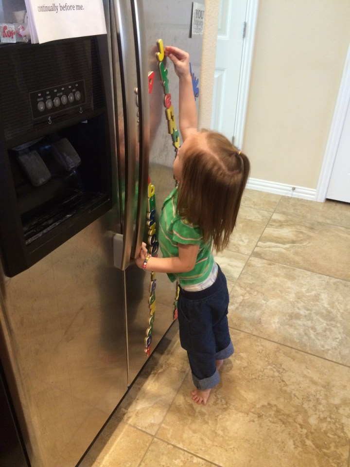 Eliza makes towers out of her magnet letters on the fridge.