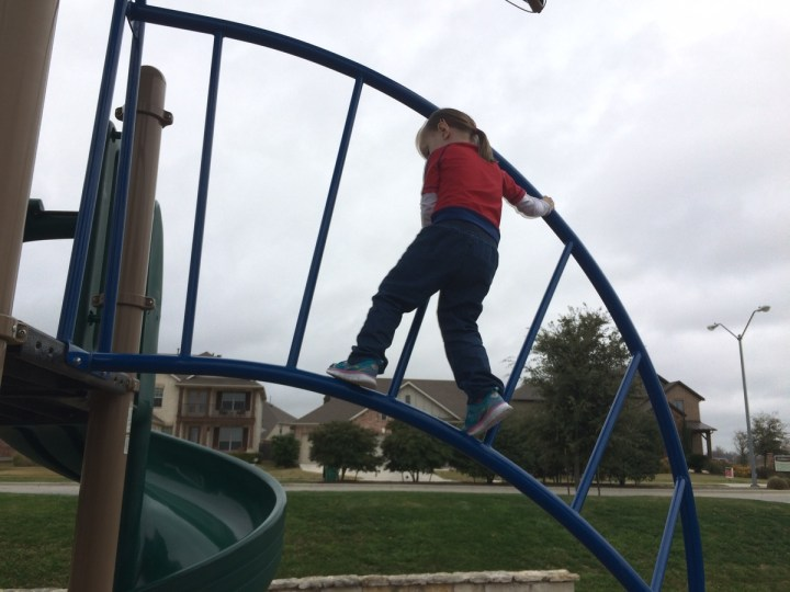 Eliza climbing on the twisty ladder at the park