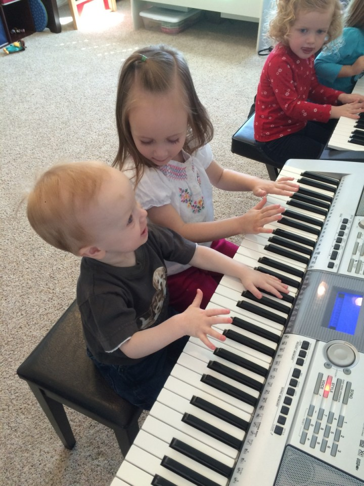 Eliza and James playing the piano at music class.