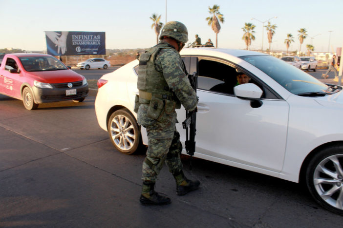 Image of a soldier talking to an automobile passenger at a checkpoint
