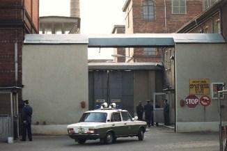 """(COL) Eingang zur Haftanstalt Rummelsburg; ein Fahrzeug der DDR - Volkspolizei biegt in die Einfahrt ein - ohne Datum (ca. 1989) lada vopos vopo stop schild gef""""ngnis"""