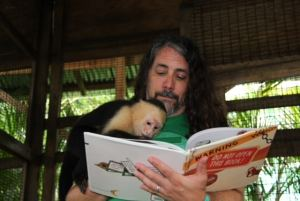 Adam Lehrhaupt reading Warning Do Not Open This Book to a monkey