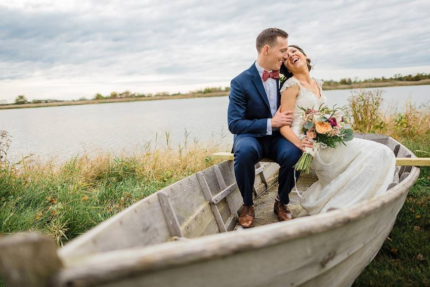 bride and groom in rowboat near river at at thousand acre farm wedding by Washington DC Wedding Photographer Adam Mason