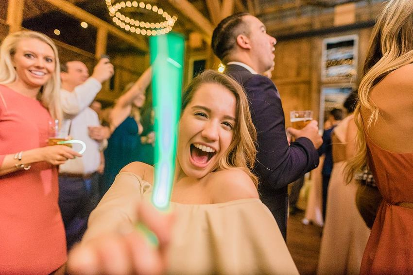 joyful wedding guest dancing with glowstick at reception during wyndridge farm wedding