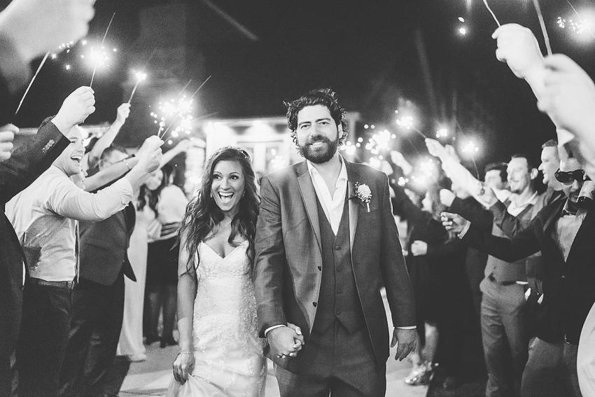 bride and groom walking down aisle during sparkler exit at wyndridge farm wedding by Washington DC Wedding Photographer Adam Mason