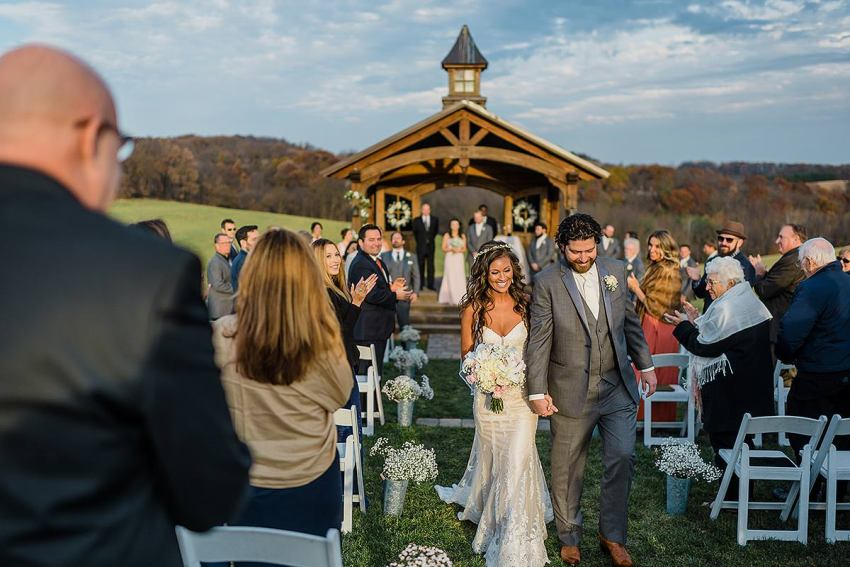 bride and groom walking down aisle at sunset during wyndridge farm wedding by Washington DC Wedding Photographer Adam Mason