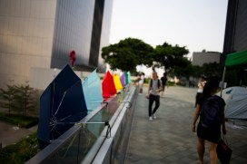 Umbrellas, the unlikely symbol of Hong Kong's largest civil disobedience movement in decades, are strapped to the railing of a pedestrian overpass, which connects Tamar Park with Admiralty Shopping Center, in central Hong Kong. (Photo: Adam McCauley)