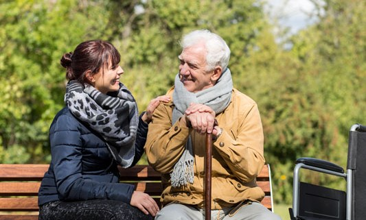 Man with walking stick and woman on a bench