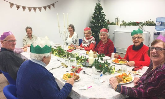 The local group seated about to eat Christmas lunch