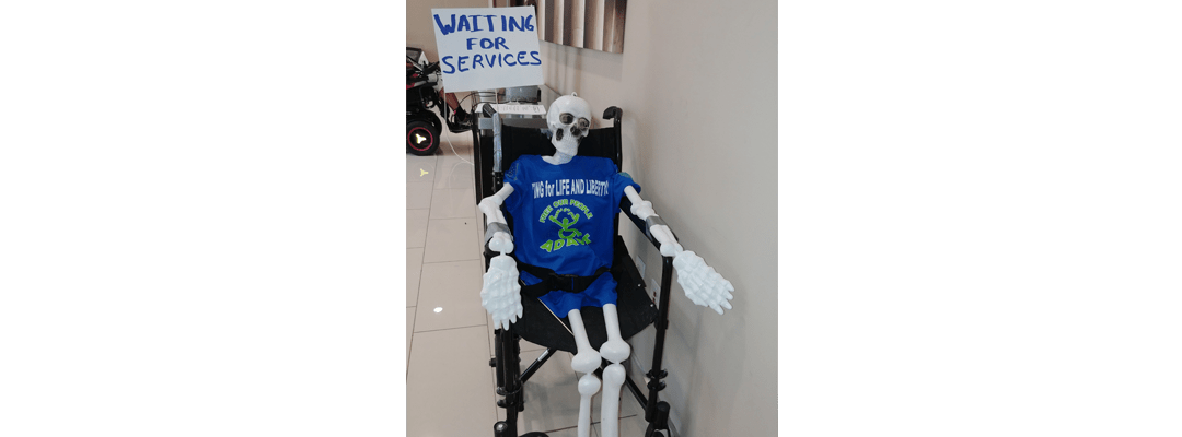 "Skeleton on a wheelchair with a sign that reads ""Waiting for services"""