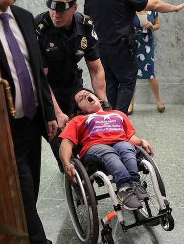 In her wheelchair being pulled by a police officer