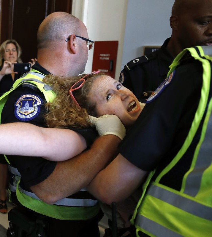 Shouting while being carried out of office by police