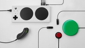 The Xbox adaptive controller - a white block - with a one-handed joystick and a number of switches attached