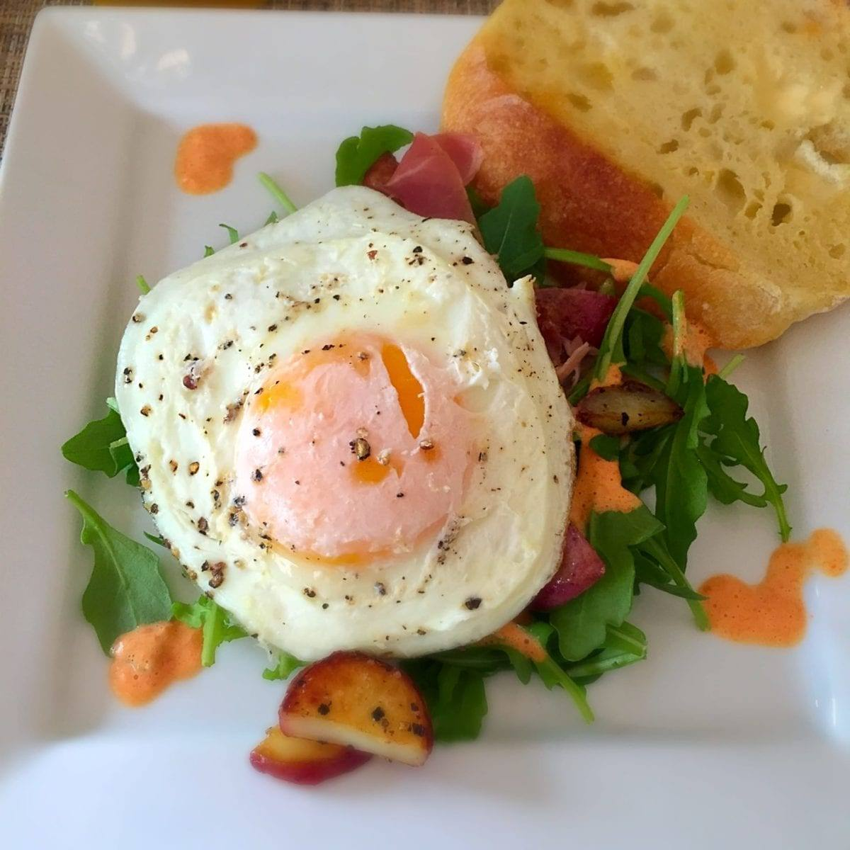 Sunny Side up Egg, over Arugula, Red Pepper Cream, Sautéed Potatoes and Prosciutto