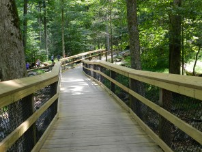 The rocky path leads to a smooth boardwalk for the end of the walk. With a bench at the very end.