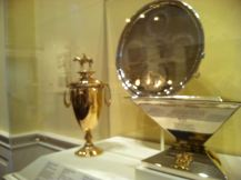 Horse racing fans! The trophies of the Triple Crown are on display in a gallery filled with horse portraits.