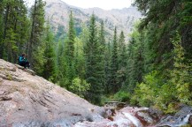 Amanda next to a small waterfall on the Lower & Upper Rowe Lake trail in Waterton Lakes National Park.