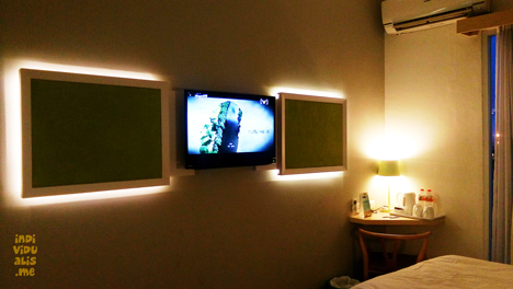 hiasan dinding dan TV di depan tempat tidur hotel maxone kamar 511