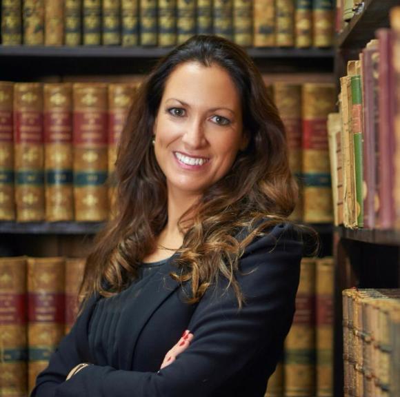 """Fotografía de la autora del artículo, """"LA IMPRESCINDIBLE LABOR DE LA ABOGACÍA DE OFICIO"""", Mª Eugenia Gay Rossell con libros de una biblioteca en el fondo."""