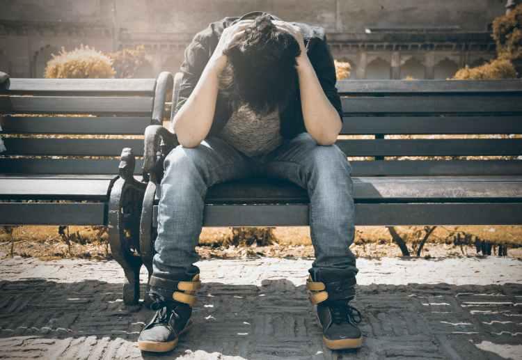 man in black shirt and gray denim pants sitting on gray padded bench
