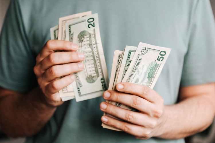 crop man counting dollar banknotes