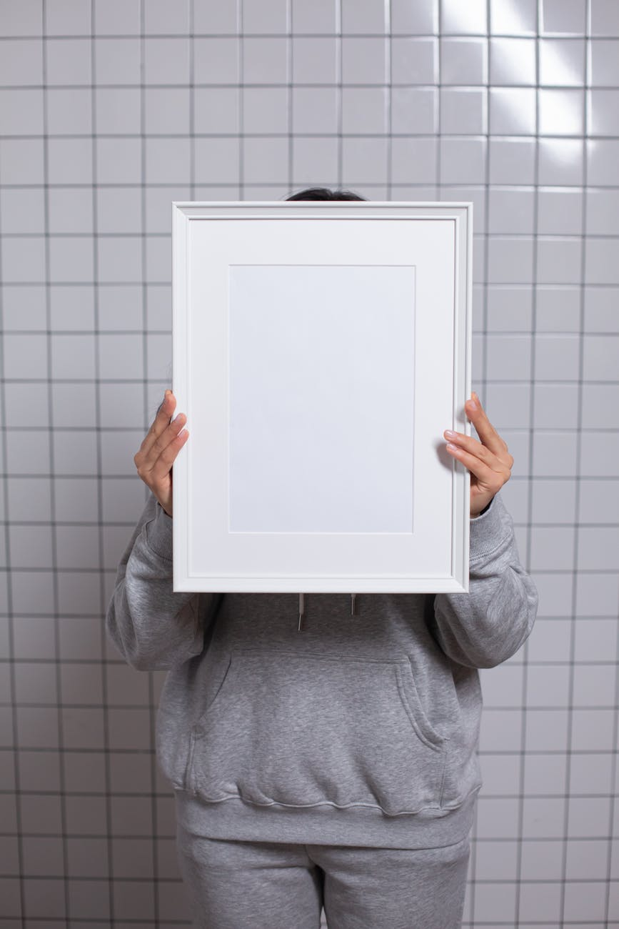 anonymous person covering face with empty white photo frame