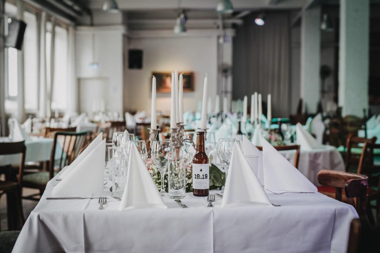 Für eine Hochzeit gedeckter Tisch im hamburger Tangostudio el Abrazo. Selbstgebrautes Craft Beer steht auf dem Tisch, die Deko besteht aus Hopfen...