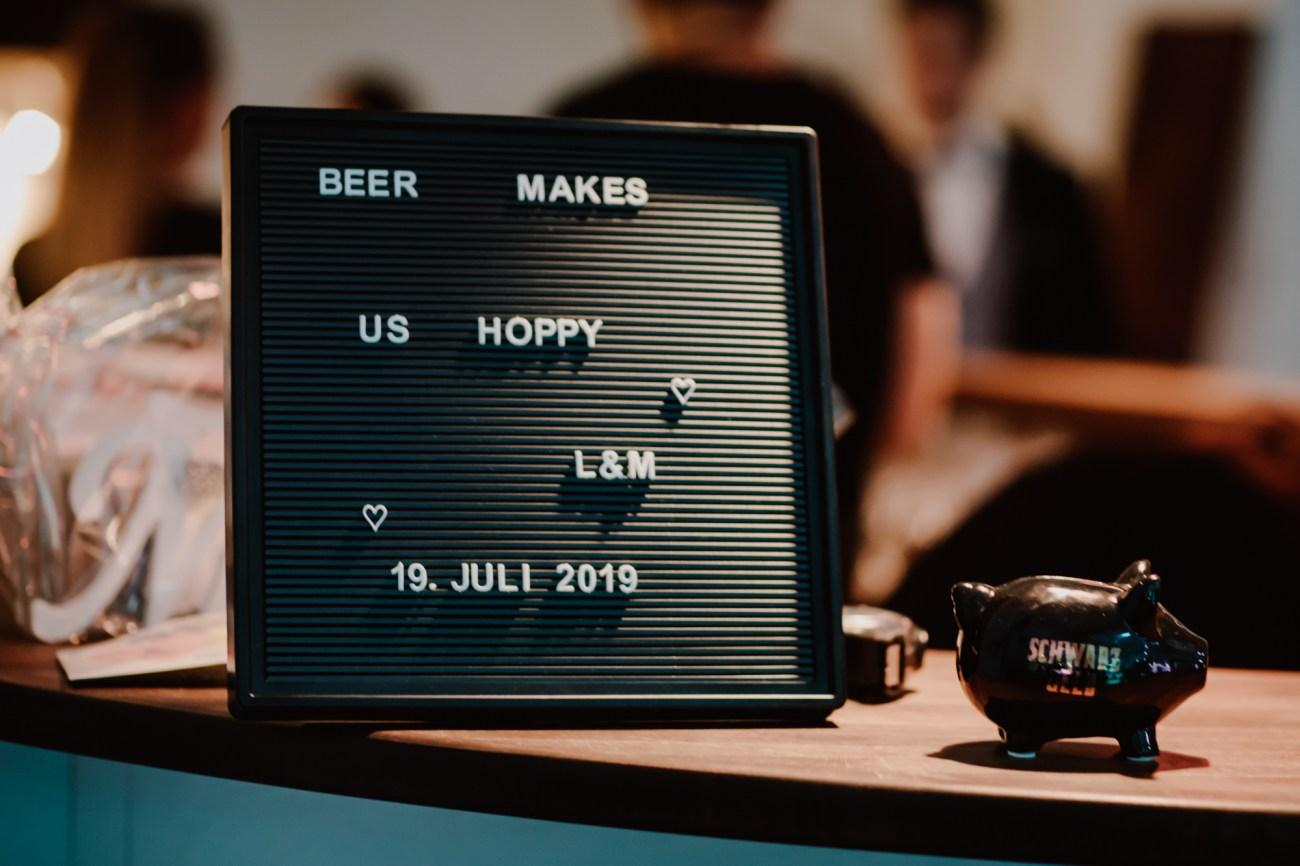 Schild bei einer Hochzeitsfeier mit der Aufschrift beer makes us hoppy
