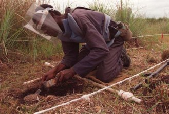 A mine clearance worker carefully clears away the dirt from a Russian made PMN land mine laid in afield next to the airport in the central Angolan town of Huambo, Tuesday February 17, 1998. Over 20 000 mines have been laid in a 10km stretch around the airport.(AP Photo/Adil Bradlow)