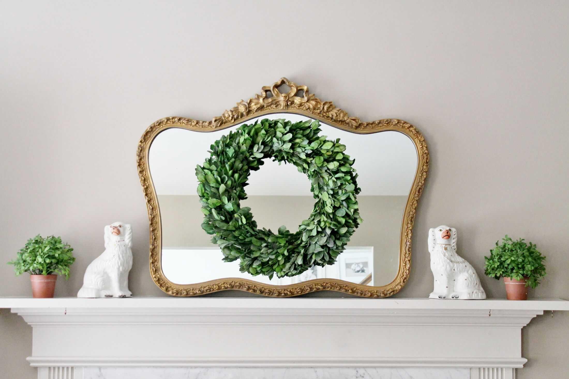 boxwood wreath hanging on vintage gold gilt mirror