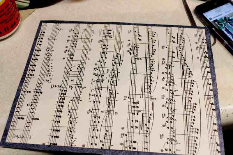 glue vintage music paper to scrapbook paper