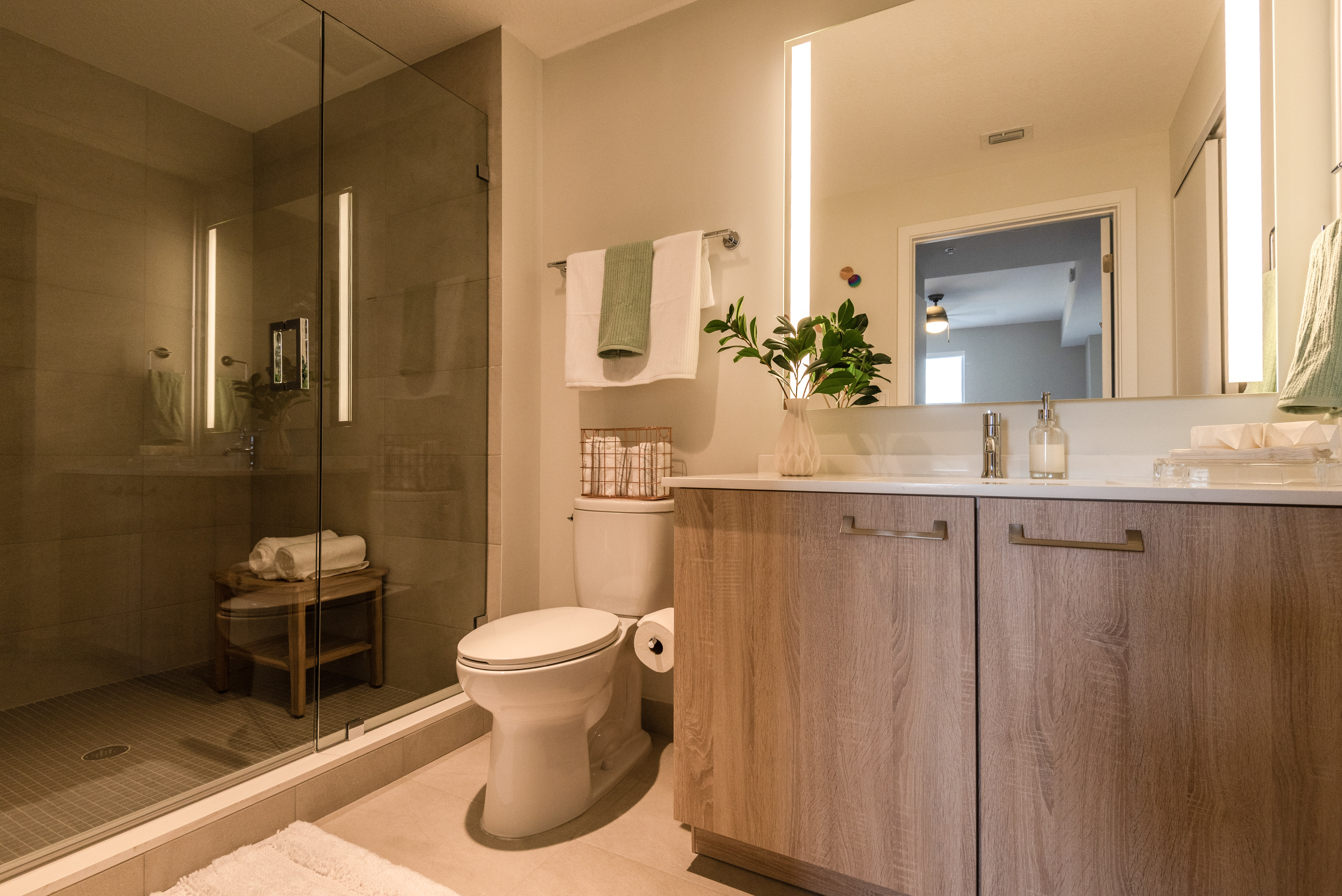 Modern bathroom with light wood vanity and walk in shower