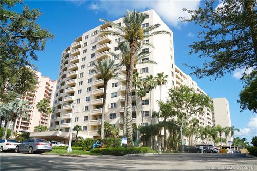 Off white high rise apartment building with palm trees and parking lot.