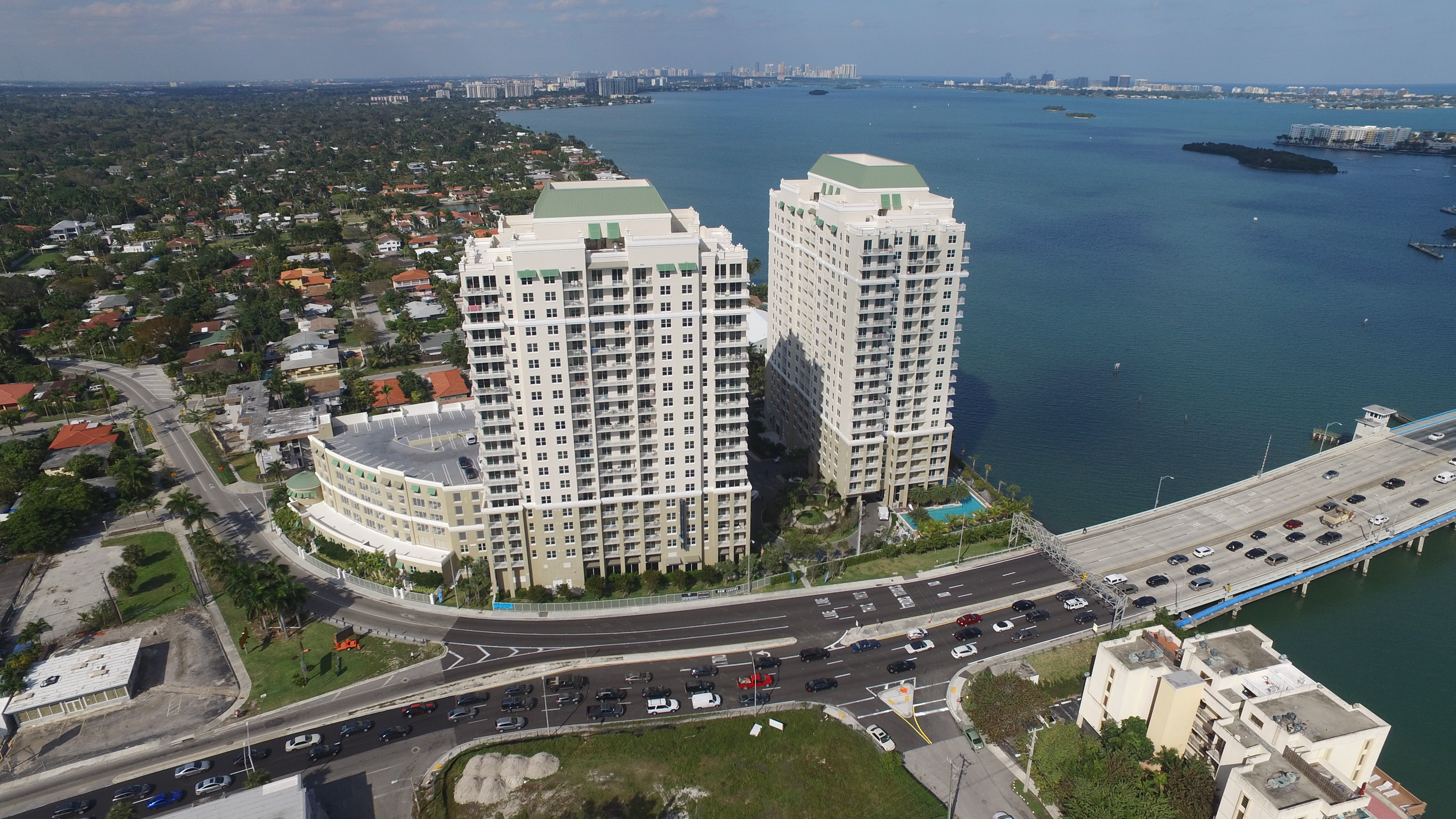 Aerial view of two waterfront high rise apartment buildings and causeway.