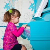 Little girl is playing the blue piano