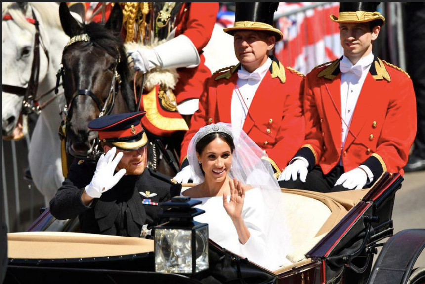 Carried Away: Prince Harry and Meghan Markle wave to the crowd during their wedding procession