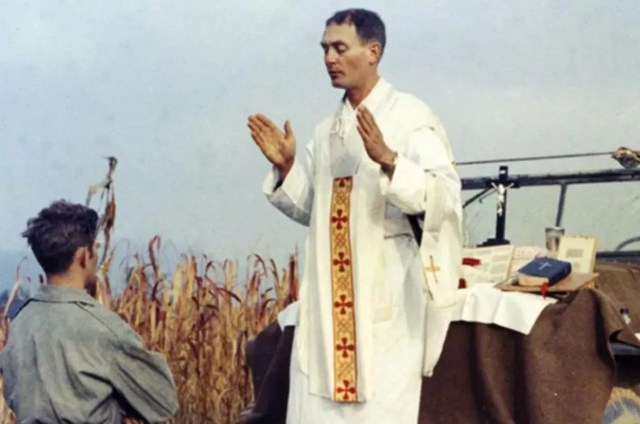Father Emil Kapaun celebrates Mass using the hood of a Jeep as his altar on Oct. 7, 1950./ Public Domain.
